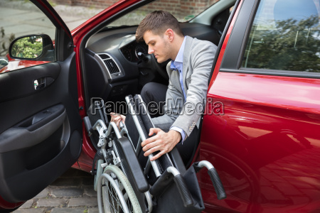 man sitting in car folding his