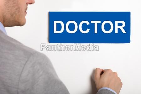 businessman, knocking, door, with, doctor, nameplate - 22722987