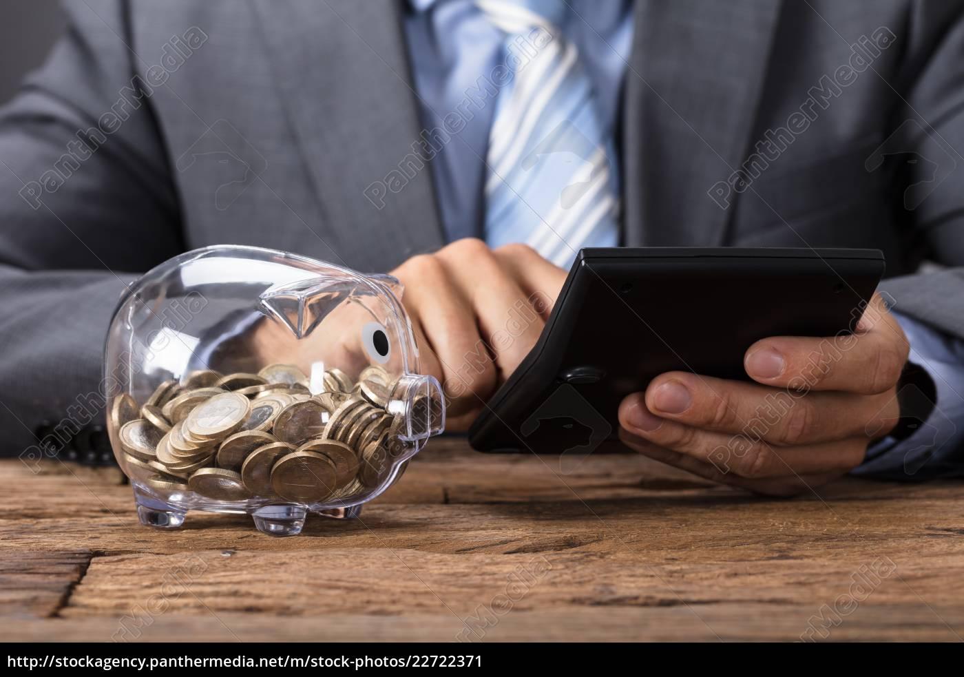 businessman, using, calculator, by, glass, piggybank - 22722371