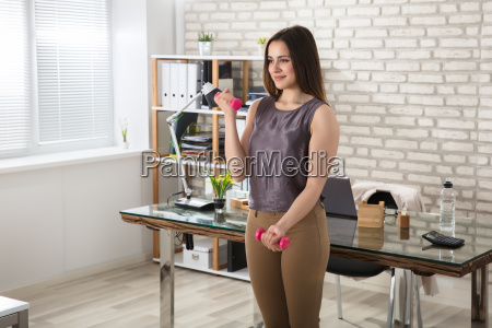 businesswoman, doing, exercise, in, office - 22722085