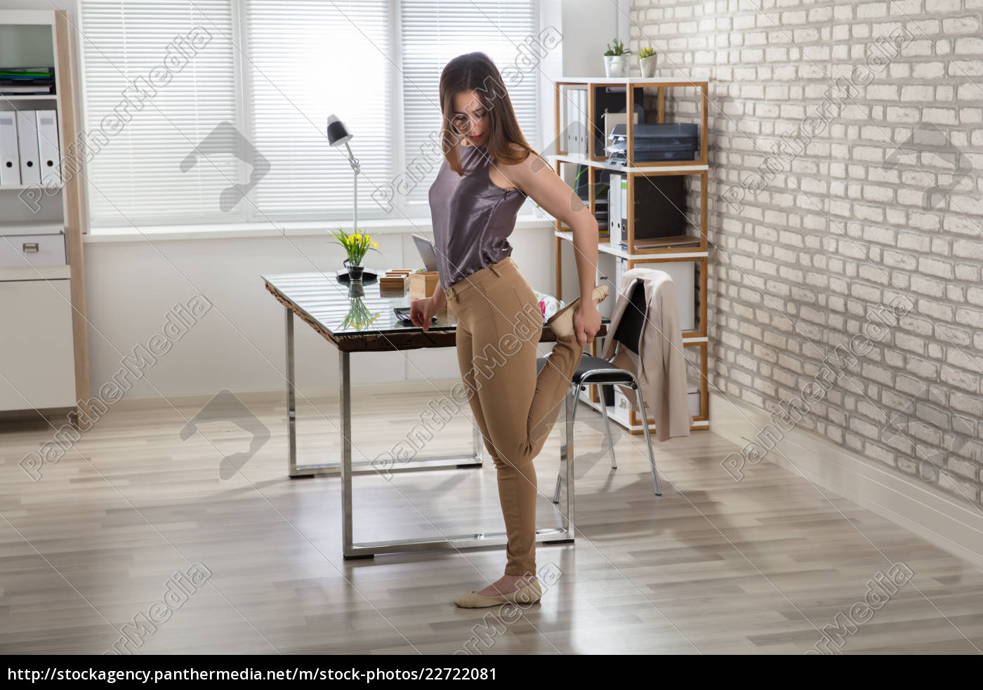 businesswoman, stretching, her, leg, in, office - 22722081