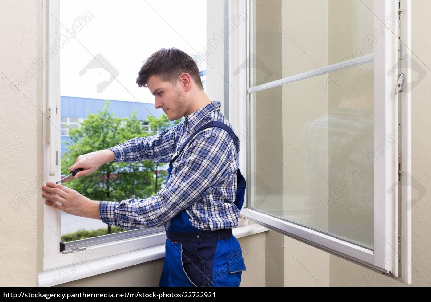 repairman, fixing, window, with, screwdriver - 22722921