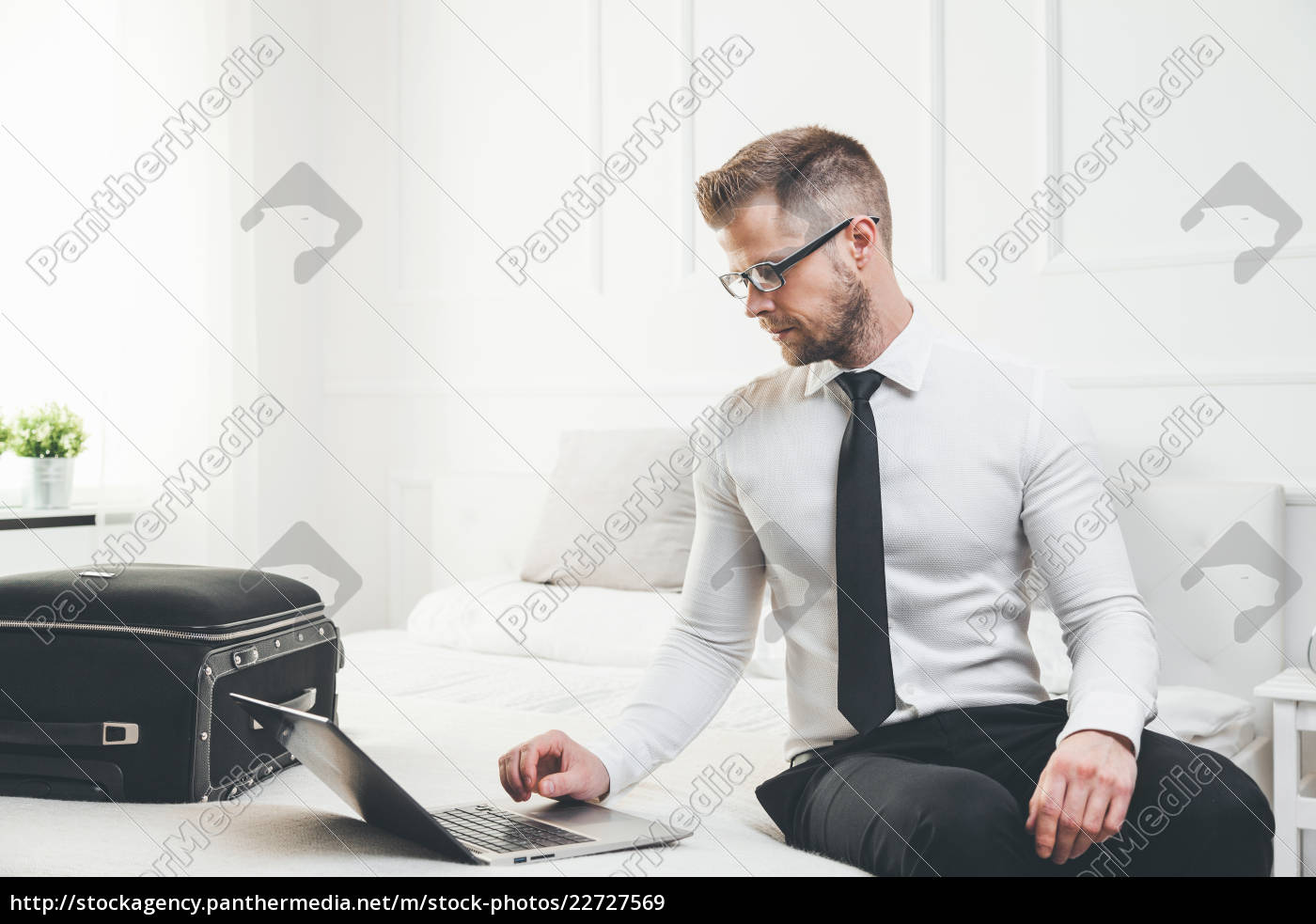 businessman, working, from, a, hotel, room - 22727569