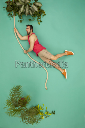 man swinging on a liana through