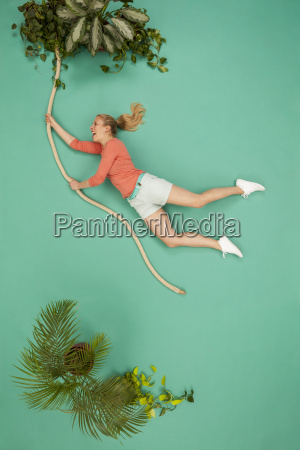 woman swinging on a liana through