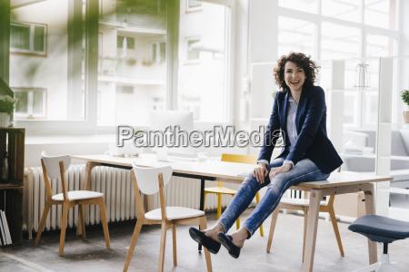 businesswoman in office sitting on desk