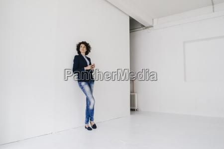 businesswoman standing in loft leaning
