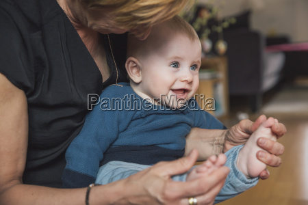 woman playing with baby boys feet