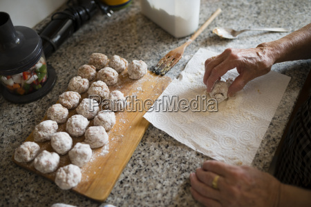 hand of senior woman preparing meatballs
