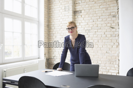 successful businesswoman standing in her office