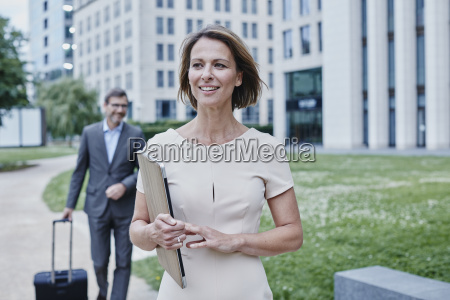 smiling businesswoman outdoors with laptop and
