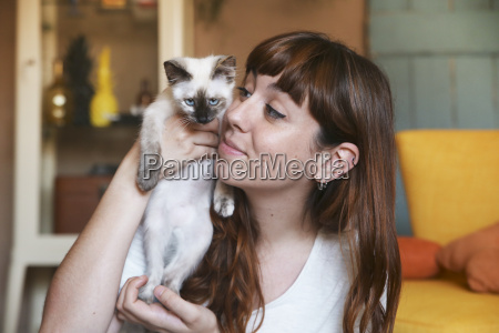 young woman with kitten at home