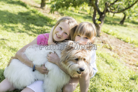 two smiling sisters cuddling with dog