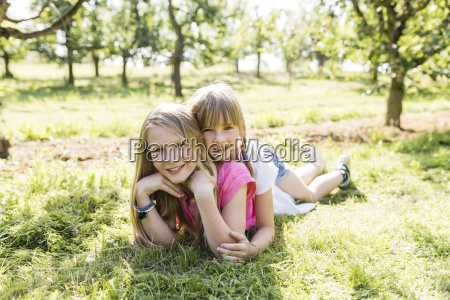 two smiling sisters lying on meadow