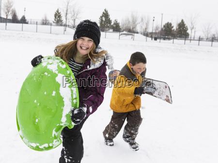 smiling boy and girl carrying toboggan