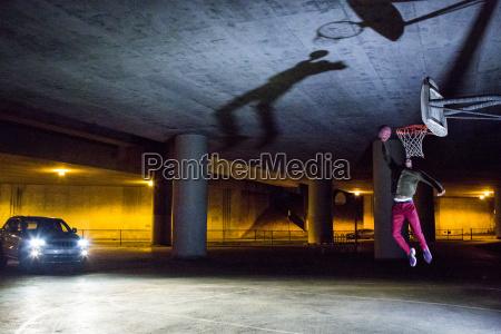 headlights shining on black man dunking
