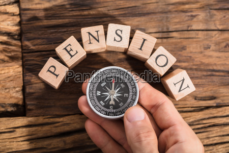 hand holding compass on pension block