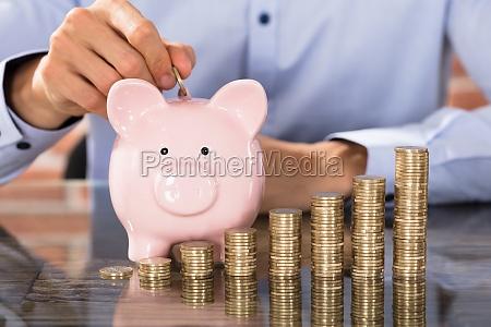 businessman insert coins in piggy bank