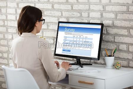 businesswoman filling survey form on computer