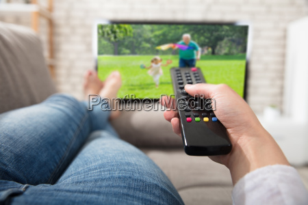 woman changing the channel with remote