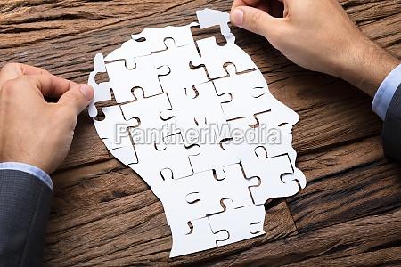 businessman making head from paper jigsaw