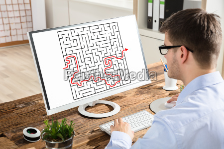 businessman solving maze on computer