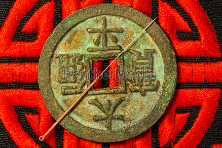 acupuncture needles on antique chinese coin