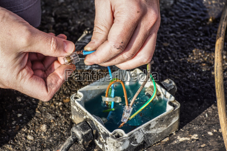 hands of electrician with terminal forbox