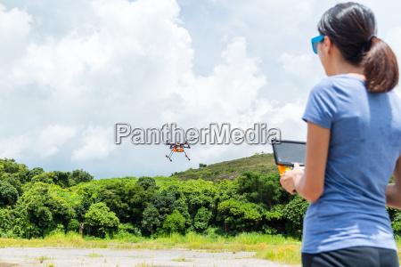 asian woman controlling drone