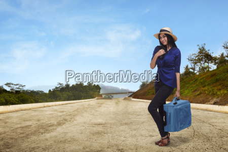 young asian woman tourist holding suitcase