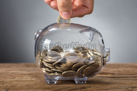 hand inserting coin in transparent piggy