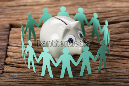 piggybank surrounded by paper people holding