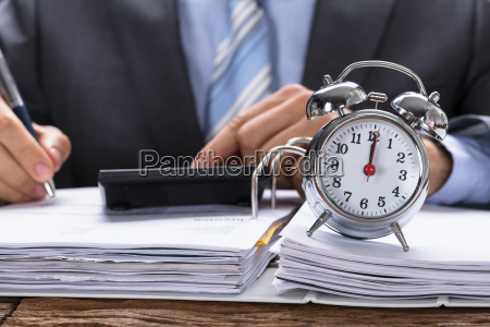 businessman calculating invoice with alarm clock