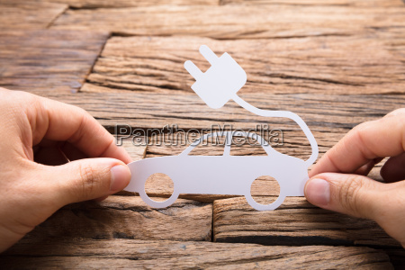 businessmans hand holding paper electric car
