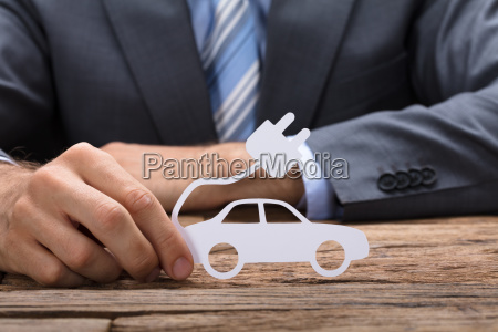 businessman holding paper electric car at