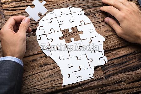 businessman holding paper jigsaw puzzle piece