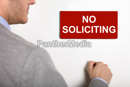 businessman knocking door with no soliciting