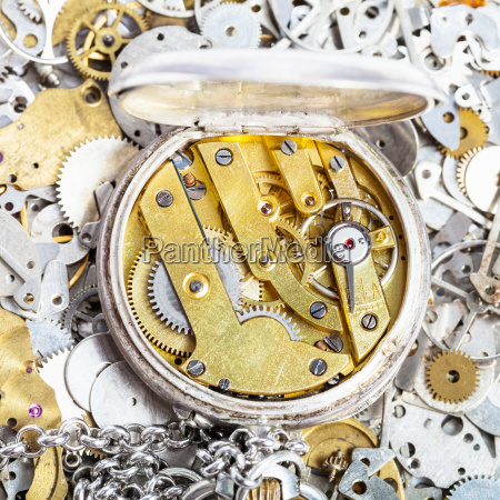 open retro pocket watch on pile