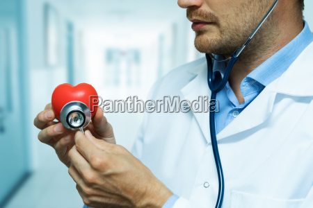 cardiologist checking red heart with stethoscope