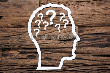 paper businessmans head outline with question