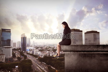 business woman sitting on building rooftop