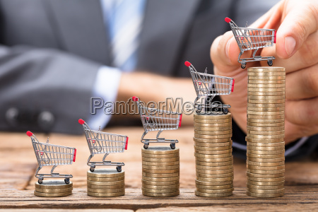 businessman placing shopping cart on stacked