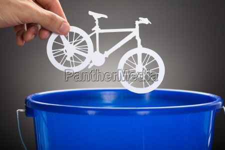 businessmans hand throwing paper bicycle in