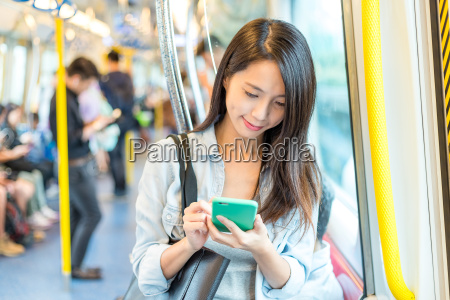 woman use of cellphone inside train