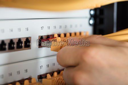 engineer plugging cables into server
