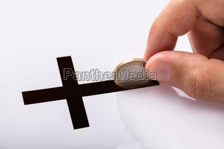 hand inserting coin in crucifix slot