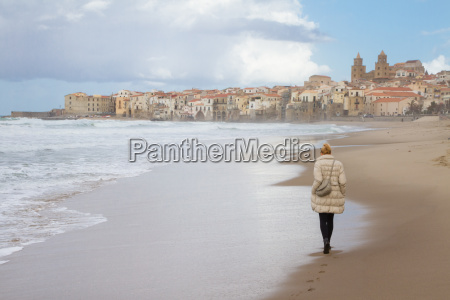 solitary woman walking the beach of