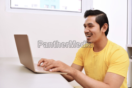 happy asian man sitting with laptop