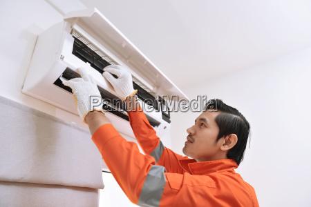 young asian male technician repairing air