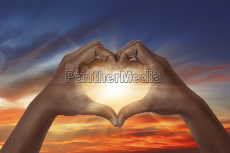 heart shaped hand with sunrise